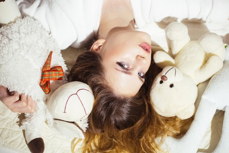 Woman with long hair in tender pajama relaxing with teddy bear. Girl with calm face lay on bed. Soft and gentle concept.