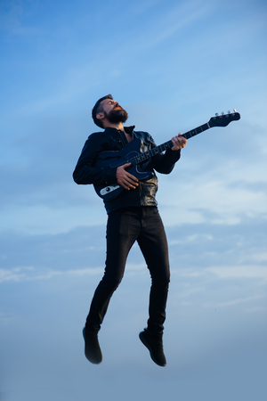 Music and freedom make him happy. Music, bearded hipster play guitar flying in blue sky. Stock Photo