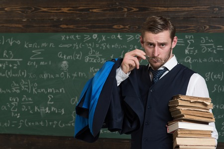 Are you serious Teacher formal wear and glasses looks suspicious, chalkboard background. Chalkboard full of math formulas. Man in end of lesson looking with wondering. Teacher finished explanation. Stok Fotoğraf