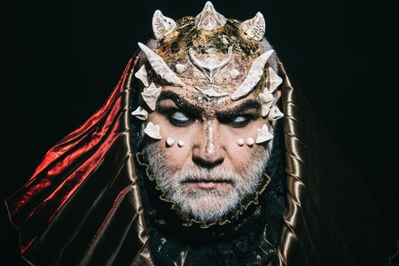 Evil demon with spikes on face and glittering skin wearing metallic hood on black background. Devil with horns raising from hell, horror concept