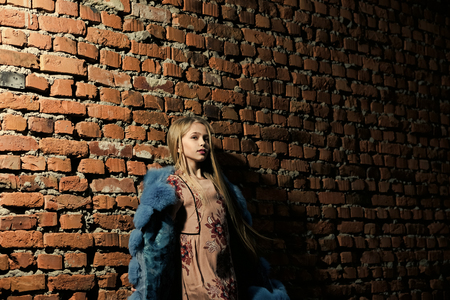 Girl posing. Little girl pose in winter jacket on brick wall, fashion. Child model with long blond hair, hairstyle and beauty. Kid fashion trend and style. Baby beauty, hair and look.