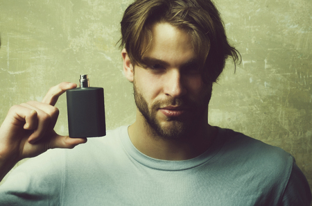 Male cologne. guy with black perfume bottle Reklamní fotografie