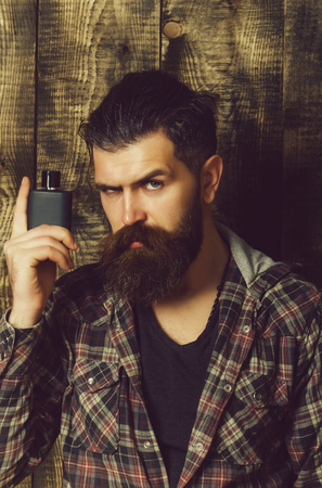 Male cologne. man posing with black perfume or cologne bottle
