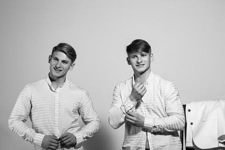 enviable bachelors. Business fashion and beauty. Twins smiling and wearing shirt. Businessman and ceo. Guys in wardrobe on grey background. Men go shopping. Stock Photo