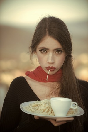 restaurant menu. Woman eating pasta as taster or restaurant critic. woman with italian pasta and tea or coffee Stock Photo