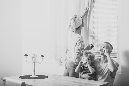 family morning. Morning routine concept. Mother and father and child sit at table in morning. Happy family spend time together,white interior and window on background Stock Photo