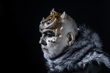 Alien, demon, sorcerer makeup. Demon on black background, copy space. Theatrical makeup concept. Senior man with white beard dressed like monster. Man with thorns or warts in fur coat