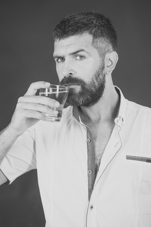 man drinking water. Man with long beard hold water glass on grey background. Imagens