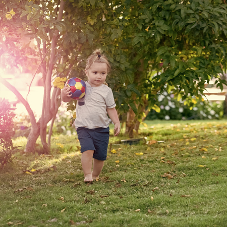 Child play with ball on green grass on idyllic day Stock Photo