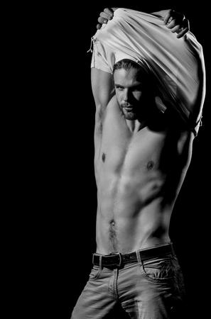 Intimo maschile. Bell'uomo spogliarsi della maglietta bianca Archivio Fotografico - 104101041