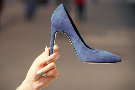 sale of shoes. shoe blue color suede on female hand on blurred background, fashion and beauty, shopping and presentation, cinderella Stock Photo
