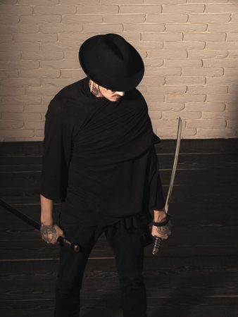 brutal samurai. Warrior in black hat and clothes, top view. Man with swords standing on wooden floor. Samurai, buddhist concept. Honor and dignity. Harakiri, suicide ritual.