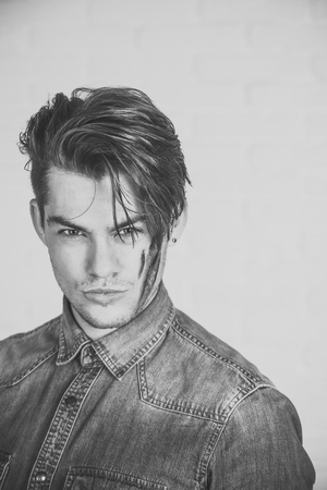 Man s dirty face. Guy with dirty face. Man posing in blue jean shirt on white background. Model with stylish hair and bristle. Hairdressing salon and barbershop. Male beauty and grooming concept Standard-Bild
