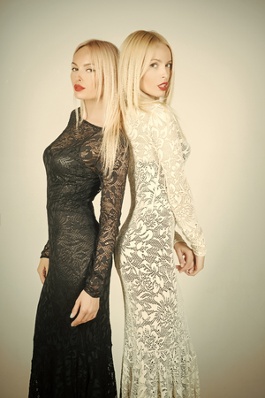 two sides of the coin. Fashion and vogue concept. Girls with blond long hair and red lips makeup. Glamour models on blue background. Woman posing in black and white lace dresses. Beauty and hairdressing.