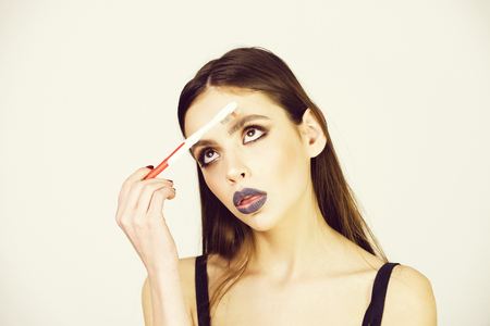 girl is fooling around. girl with teeth brush, has fashionable makeup