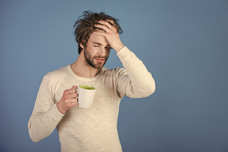 morning hangover. Sleepy guy with tea cup has headache on blue background. Stock Photo