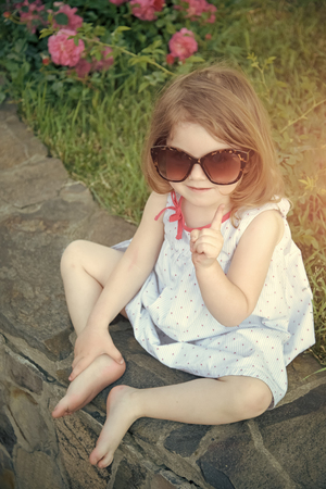 child points. Baby girl smiling in sunglasses with raised finger on stone border with bare feet. Child and childhood. Summer vacation concept. Standard-Bild