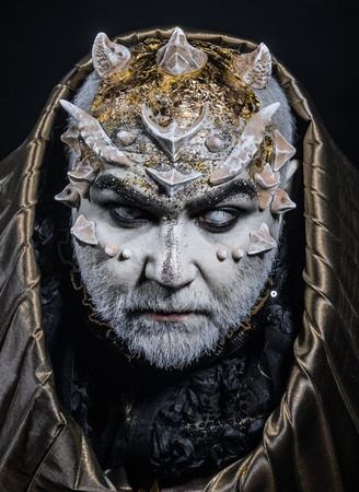 Man with thorns or warts, face covered with glitters. Demon with golden hood on black background. Senior man with white beard dressed like monster. Alien, demon, sorcerer makeup. Fantasy concept