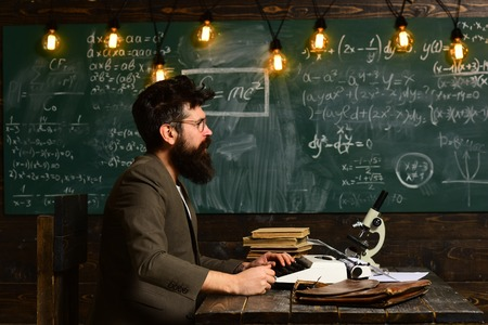 Side view portrait of stylish man with old school vintage typewriter on wooden table, typing story Reklamní fotografie