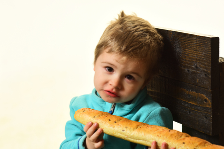 Bakery shop concept. Little boy with french baguette in bakery shop. Cute child with fresh bread in bakery shop. Bakery shop and products. The only bread worth eating