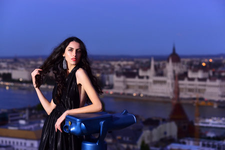 Luxury woman in evening dress with view on city. Sexy girl in elegant dress. Modern life with princess in celebrity style. Fashion and beauty of business lady. Girl with glamour makeup.