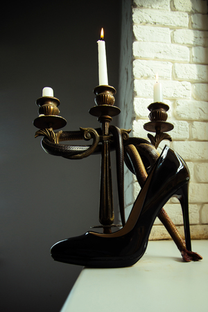 Design shoe of black leather stand on high heel with snake wrapped around candle holder. Design footwear and still life design 版權商用圖片