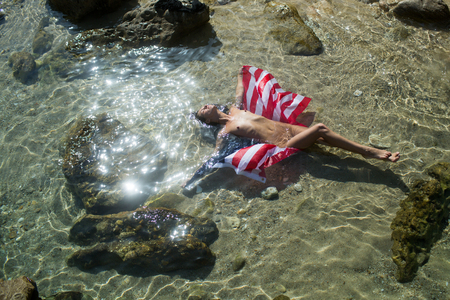 independence day, american flag in water with woman and man. Summer holidays and paradise travel vacation. Couple in love with body relax on beach. Love relations of couple in sea.
