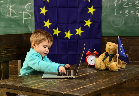 Ready for school. Little boy use laptop, ready for school. Child ready for school in classroom with eu flag. Computer technology for ready for school. Hooked on learning
