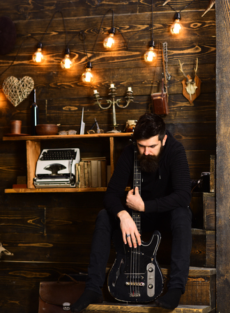 Connection through music. Man bearded musician enjoy evening with bass guitar, wooden background. Man with beard holds black electric guitar. Guy sits thoughtful dreamy in cozy warm atmosphere