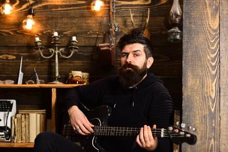 Guitar as hobby. Man bearded musician enjoy evening with bass guitar, wooden background. Man with beard holds black electric guitar. Guy in cozy warm atmosphere play favourite music Stock Photo
