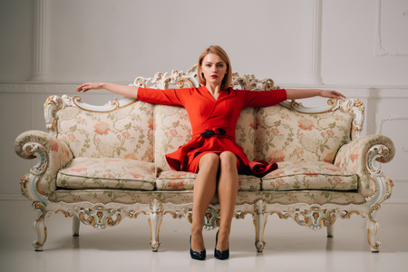 business woman in red dress on luxury sofa. business lady waiting for meeting. business woman relax after working day. agile business. welcome on board.