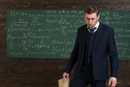 Exacting teacher. Teacher formal wear and glasses looks smart, chalkboard background. Professor exacting and strict holds book. Man with high expectations looks unsatisfied with students knowledge