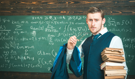 Clear explanation. Teacher formal wear and glasses looks smart, chalkboard background. Man in end of lesson takes off eyeglasses. Teacher finished explanation. Chalkboard full of math formulas Stok Fotoğraf