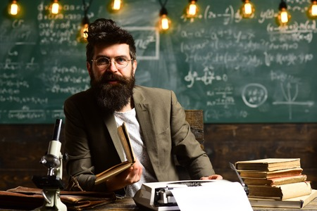 Scientist in glasses type on vintage typewriter. Scientist with beard typewrite research paper with microscope and books, future and archaism Stock Photo