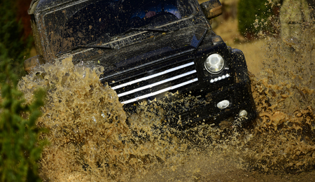 Auto racing on fall nature background. Competition, energy and motorsport concept. Off road vehicle or SUV crossing puddle with dirt splash. Car racing in autumn forest