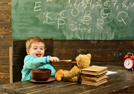 Healthy lunch in school cafeteria. Little child share healthy lunch with toy friend. Boy enjoy healthy lunch with teddy bear. Healthy lunch food. No junk, know health Stock Photo