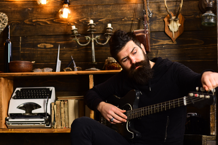 Guitar as hobby. Man bearded musician enjoy evening with bass guitar, wooden background. Guy in cozy warm atmosphere play favourite music. Man with beard holds black electric guitar Stock Photo