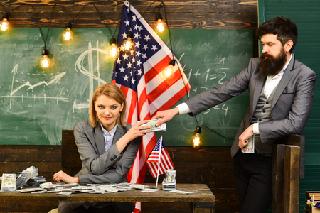 business Woman with dollar money for bribe for bearded man. business woman and bearded man at usa flag. Stok Fotoğraf