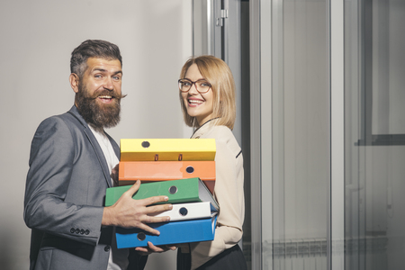 Business man help businesswoman to carry binders in office. Business cooperation and teamwork Stock Photo