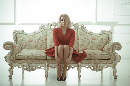 mujer anfitriona da la bienvenida a los invitados. búsqueda de trabajo de azafata. la anfitriona de la recepción del hotel se sienta en el sofá en vestido rojo. anfitriona Foto de archivo
