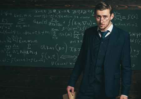 Exacting teacher. Man with high expectations looks unsatisfied with students knowledge. Professor exacting and strict holds book. Teacher formal wear and glasses looks smart, chalkboard background