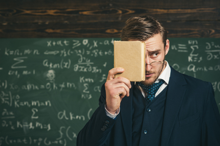 Teacher insists on need to memorize information. You should remember. Teacher formal wear and glasses looks smart, chalkboard background. Man unshaven holds book in front of face. Education concept 版權商用圖片