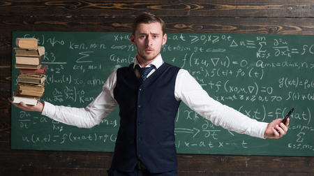 Man teacher balancing in hands pile of books and smartphone as symbol analog and digital information storages. . Balance concept. Modern against outdated. Teacher formal wear, chalkboard background