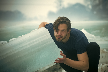 Male fashion portrait. Power and strength of man with frozen hummock. Winter holiday and activity. Cracked ice at Hercules guy in Christmas. Cold weather and ice age. Man hold big ice block.
