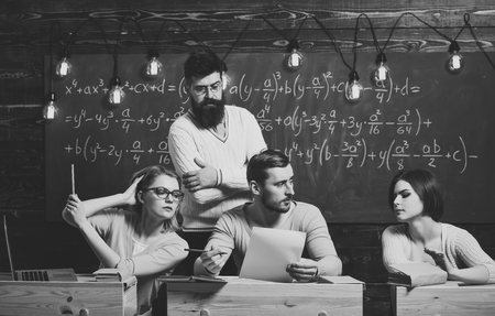 College education concept. Students, group mates speaking, asking for advice or cheating while teacher watching them. Bearded teacher, lecturer, professor watching students during test, exam, lesson. Stock Photo