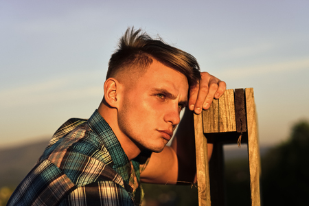 thoughtful man. man rest at wooden fence, tired. Man thinking and dreaming in sunset. Stock Photo