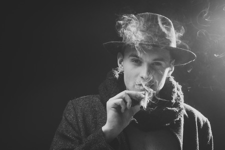 Mysterious man. Man in coat, hat smoking cigar, dark background. Macho on mysterious face, detective, investigator, agent. Guy in old fashioned outfit looks mysterious with cigar and smoke. 스톡 콘텐츠