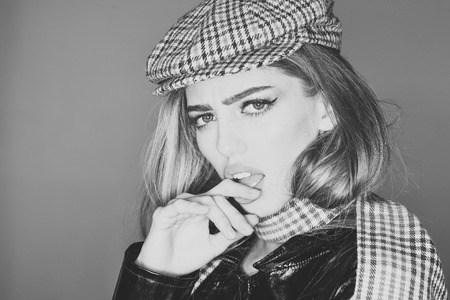Fashion accessories concept. Woman on scandalized face with make up with checkered accessories. Lady in stylish outfit, close up. Girl with long hair wears kepi, scarf, grey background, copy space. Stock fotó