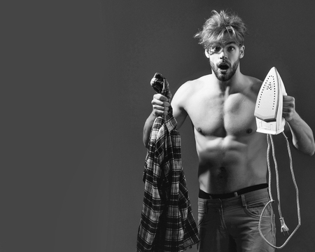 How to use an iron. Young handsome topless man with messy hair screams with white iron and plaid shirt in his hand in beige pants in front of dark background, copy space Stock Photo