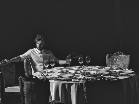 Restaurant critic. Handsome young man with beard and blond hair drinks wine from glass sitting at table with leftovers or residues food on dirty plates after banquet dinner in restaurant on dark background